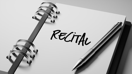 Closeup of a personal agenda setting an important date writing with pen. The words Recital written on a white notebook to remind you an important appointment. Stock Photo