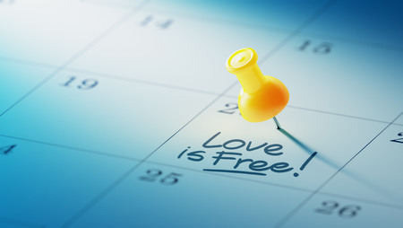 yellow push pin: Concept image of a Calendar with a yellow push pin. Closeup shot of a thumbtack attached. The words Love is Free written on a white notebook to remind you an important appointment. Stock Photo