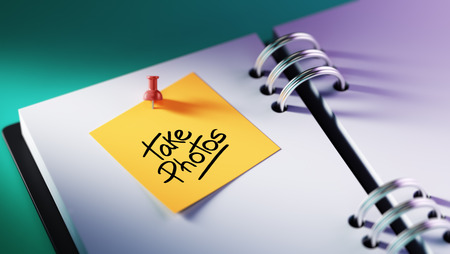 take a note: Closeup Yellow Sticky Note paste it in a notebook setting an appointment. The words Take photos written on a white notebook to remind you an important appointment. Stock Photo