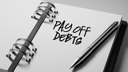 pay off: Closeup of a personal agenda setting an important date writing with pen. The words Pay off debts written on a white notebook to remind you an important appointment. Stock Photo