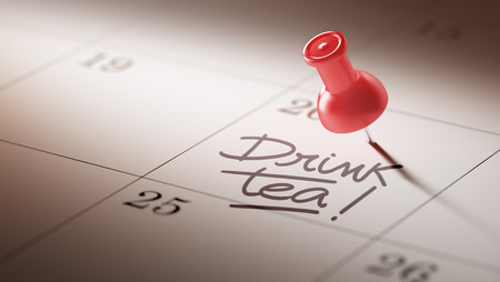 herbal knowledge: Concept image of a Calendar with a red push pin. Closeup shot of a thumbtack attached. The words Drink Tea written on a white notebook to remind you an important appointment.