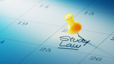 yellow push pin: Concept image of a Calendar with a yellow push pin. Closeup shot of a thumbtack attached. The words Study Law written on a white notebook to remind you an important appointment.