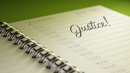 judgement day: Closeup of a personal calendar setting an important date representing a time schedule. The words Justice written on a white notebook to remind you an important appointment. Stock Photo