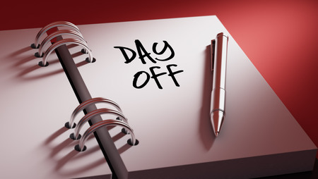 Closeup of a personal agenda setting an important date writing with pen. The words Day off written on a white notebook to remind you an important appointment.