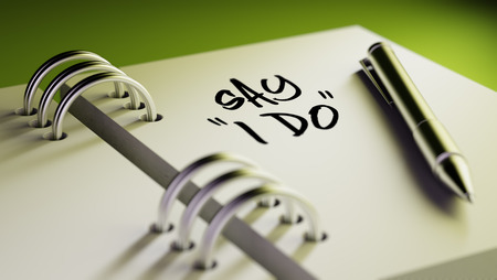 """Closeup of a personal agenda setting an important date writing with pen. The words Say """"I DO"""" written on a white notebook to remind you an important appointment. Imagens"""