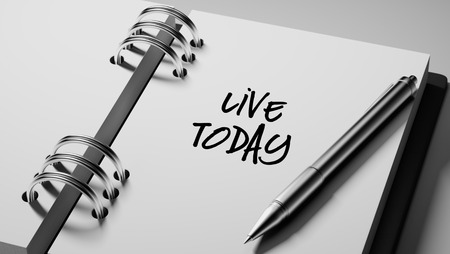 living moment: Closeup of a personal agenda setting an important date writing with pen. The words Live today written on a white notebook to remind you an important appointment.