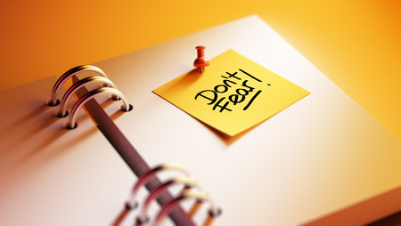 dont: Closeup Yellow Sticky Note paste it in a notebook setting an appointment. The words Dont Fear written on a white notebook to remind you an important appointment.