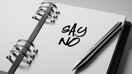 denying: Closeup of a personal agenda setting an important date writing with pen. The words Say NO written on a white notebook to remind you an important appointment.