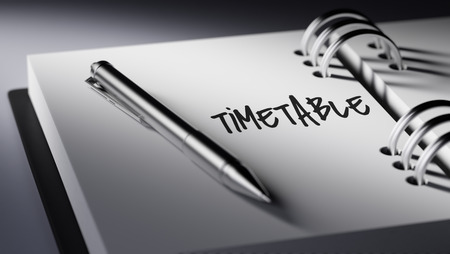 cronologia: Closeup of a personal agenda setting an important date writing with pen. The words Timetable written on a white notebook to remind you an important appointment.