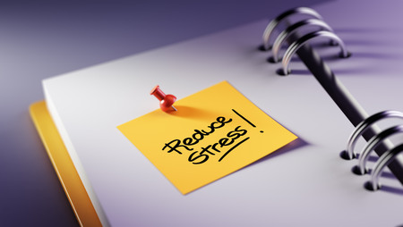 elimination: Closeup Yellow Sticky Note paste it in a notebook setting an appointment. The words Reduce Stress written on a white notebook to remind you an important appointment. Stock Photo