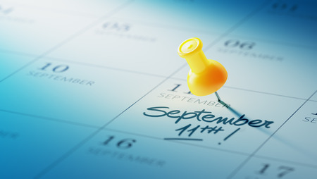 yellow push pin: Concept image of a Calendar with a yellow push pin. Closeup shot of a thumbtack attached. The words September 11th written on a white notebook to remind you an important appointment. Stock Photo