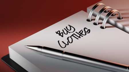 clothes organizer: Closeup of a personal agenda setting an important date writing with pen. The words Buy Clothes written on a white notebook to remind you an important appointment. Stock Photo