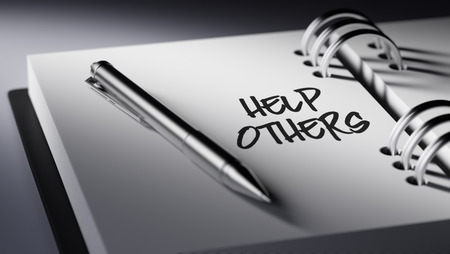 helping others: Closeup of a personal agenda setting an important date writing with pen. The words Help Others written on a white notebook to remind you an important appointment. Stock Photo