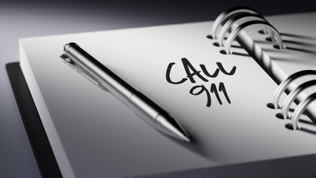 personal call: Closeup of a personal agenda setting an important date writing with pen. The words Call 911 written on a white notebook to remind you an important appointment. Stock Photo