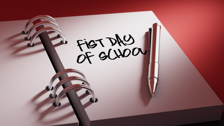 initiate: Closeup of a personal agenda setting an important date writing with pen. The words First day of school written on a white notebook to remind you an important appointment. Stock Photo