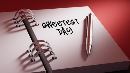 sweetest: Closeup of a personal agenda setting an important date writing with pen. The words Sweetest Day written on a white notebook to remind you an important appointment. Stock Photo