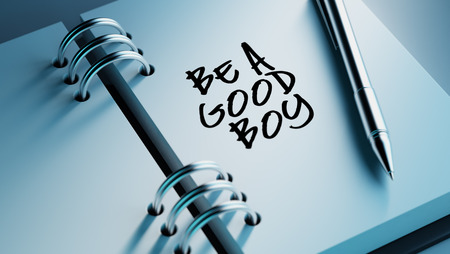 good boy: Closeup of a personal agenda setting an important date writing with pen. The words Be a good boy written on a white notebook to remind you an important appointment.