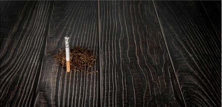 a burning cigarette with pile of tobacco on a wooden background