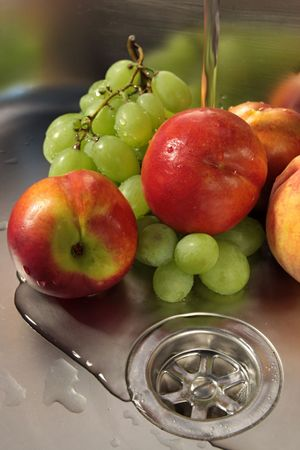 Washing fruits in stainless steel sink photo