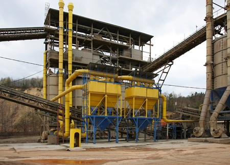 gravel pit: Stone quarry with silos, conveyor belts and piles of stones.