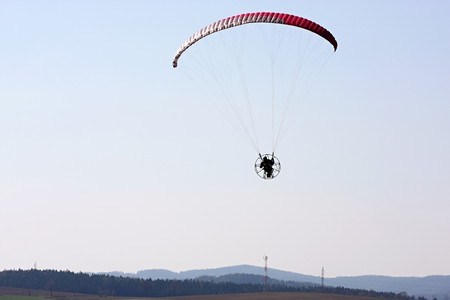 high powered: A powered paraglider pilot in flight over the landscape Stock Photo
