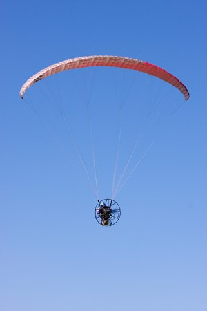 A powered paraglider pilot in flight with a blue sky in the background  photo