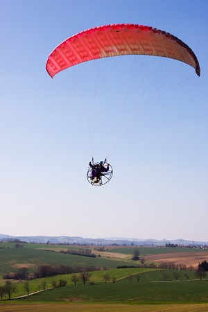 airfoil: A powered paraglider pilot in flight over the landscape Stock Photo