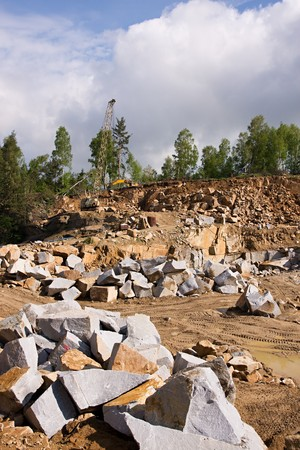 Granite quarry mining in the background crane with a digger Stock Photo