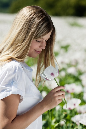 Handsome girl smells white poppies photo