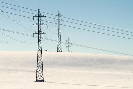 High voltage electricity power pylon on snowy field photo