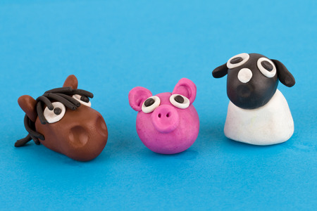 Cute plasticine farm animals collection isolated on blue background. Pig, horse, sheep. photo