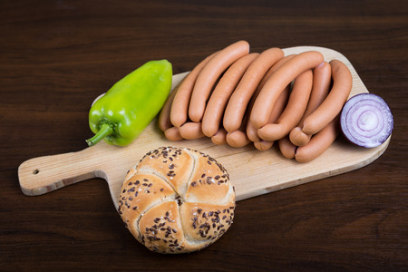 arranged: Sausages arranged on cutting board with baguette