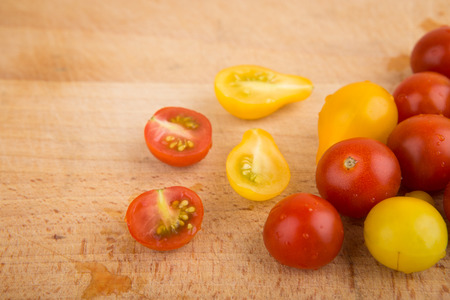 lycopene: Red and yellow cherry tomatoes on a wooden cutting board