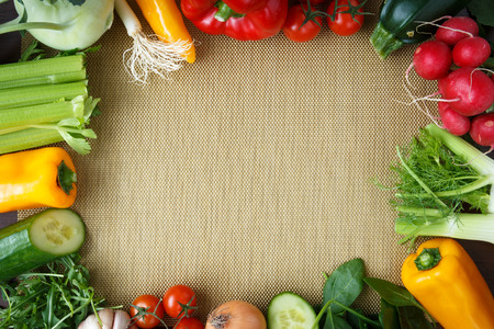 placemats: Healthy eating background. Different vegetables on golden kitchen placemats. Stock Photo