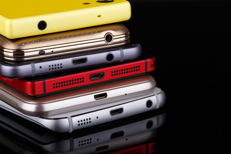 electronical: Heap of electronical devices close up - smartphones on black background