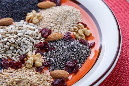 avena en hojuelas: Surtido de semillas secas frescas usados ??como ingredientes en la cocina. Girasol, sésamo, semillas de lino, semillas de amapola, la chía, nueces, copos de avena y arándanos en la placa.
