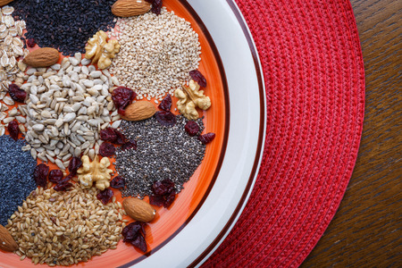 linseed: Assortment of fresh dried seeds Used as ingredients in cooking. Sunflower, sesame, linseed, poppy, chia, nuts, rolled oats and Cranberries on plate.