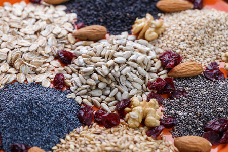 avena en hojuelas: Assortment of fresh dried seeds Used as ingredients in cooking. Sunflower, sesame, linseed, poppy, chia, nuts, rolled oats and Cranberries on plate.
