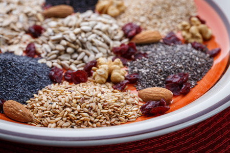 Assortment of fresh dried seeds Used as ingredients in cooking. Sunflower, sesame, linseed, poppy, chia, nuts, rolled oats and Cranberries on plate.