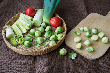 Brussels sprouts (Brassica oleracea) tomato, leek in a basket Stock Photo