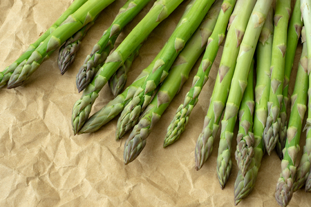 Raw garden asparagus stems. Fresh green spring vegetables on brown wrapping paper. (Asparagus officinalis). Stockfoto