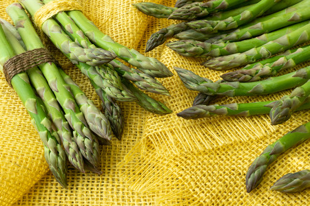 Bunches of asparagus tied with twine on a burlap background. Asparagus officinalis.
