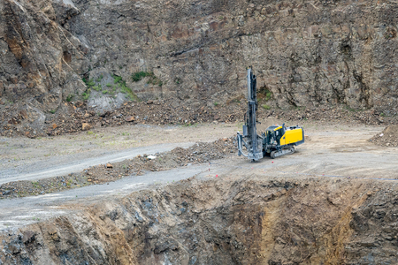 Opencast mining quarry with mining drilling machine. Mining in the granite quarry. Mining industry.