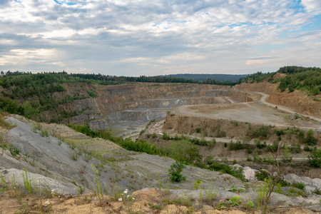 Opencast mining quarry with machinery. Quarrying of stones for construction works. Mining industry in quarry. 版權商用圖片
