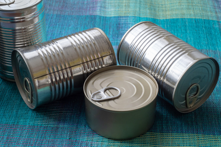 Tin cans with food. Conserved food. Closeup of a group of aluminium cans.