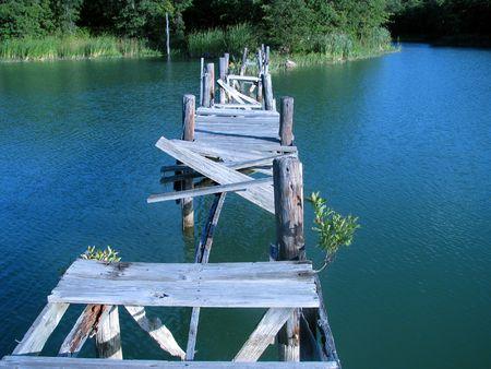 Gebroken brug op een rustig meertje. Stockfoto