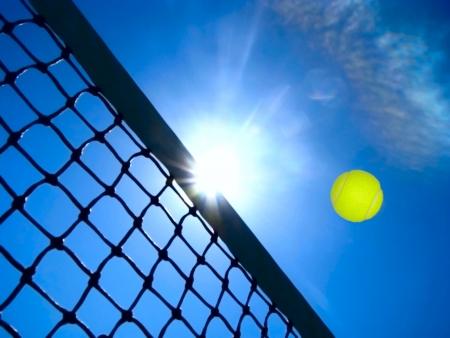 raqueta de tenis: Juego de tenis bajo el cielo azul.