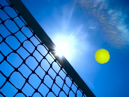 Tennis game under the blue sky.