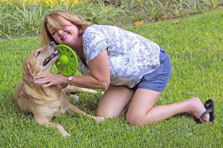 Mature woman playing with her dog. photo