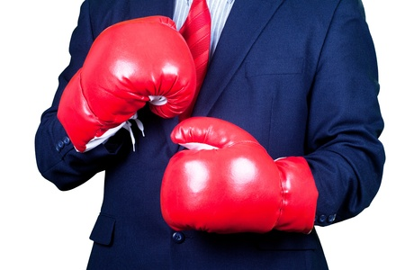 Businessman in suit waering red gloves ready for boxing